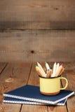 Bleistifte in einem Becher auf einem Holztisch Lizenzfreie Stockfotos