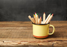Bleistifte in einem Becher auf einem Holztisch und einer Tafel Stockfoto