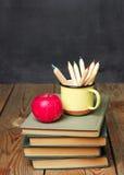 Bleistifte in einem Becher, in den Büchern und im Apfel Stockbilder