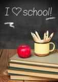 Bleistifte in einem Becher, in den Büchern und im Apfel Stockfotos