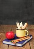 Bleistifte in einem Becher, in einem Buch und in einem Apfel Lizenzfreies Stockbild