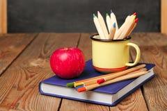 Bleistifte in einem Becher, in einem Buch und in einem Apfel Lizenzfreie Stockfotografie