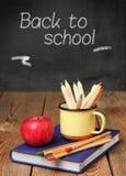Bleistifte in einem Becher, in einem Buch und in einem Apfel Stockfotografie
