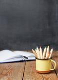 Bleistifte in einem Becher, in einem offenen Notizbuch und in einer Tafel Lizenzfreie Stockfotografie
