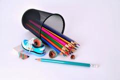 Bleistifte in einem Glas, in einem Bleistiftspitzer und in einem Radiergummi auf einem weißen Hintergrund Stockfotos
