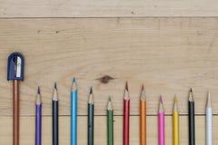 Bleistifte färben und Bleistiftspitzer auf hölzerner Tabelle Lizenzfreie Stockfotografie