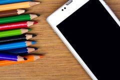Bleistifte färben und intelligentes Telefon auf hölzernem Hintergrund Stockfotografie