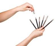 Bleistifte für Make-up in den weiblichen Händen lokalisiert auf Weiß Stockfotografie