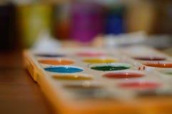 Bleistifte, Farbe und Papier auf dem Tisch Lizenzfreie Stockfotografie