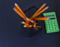 Bleistifte im Stand und im Taschenrechner auf schwarzem Hintergrund Lizenzfreie Stockfotografie