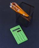 Bleistifte im Stand und im Taschenrechner auf schwarzem Hintergrund Lizenzfreie Stockbilder