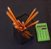 Bleistifte im Stand und im Taschenrechner auf schwarzem Hintergrund Lizenzfreies Stockfoto