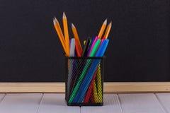 Bleistifte im Stand vor schwarzer Schulbehörde Stockfotografie