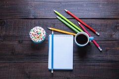 Bleistifte, Kaffee, kleiner Kuchen und Notizbuch Stockfotos
