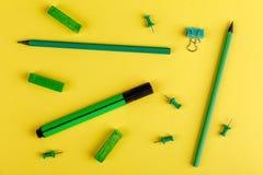 Bleistifte, Markierungen, Zeichenstifte und Klipp des Grüns, auf einem gelben Hintergrund Lizenzfreie Stockfotos