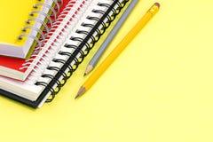 Bleistifte mit mehrfarbigen Notizbüchern für Untersuchungen über gelbes backgr Stockfotografie