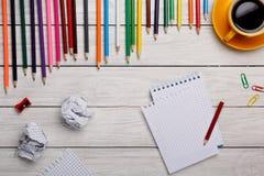 Bleistifte mit Notizblock und zerknittertem Papier auf weißer Tabelle Lizenzfreies Stockbild