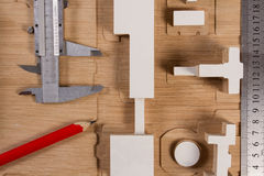 Bleistifte, Modellbauten, Maßstab und Tasterzirkel auf einer Holzoberfläche Stockfoto
