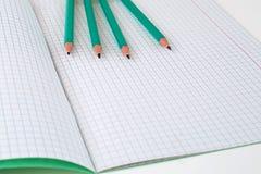 Bleistifte nahe bei dem Schulnotizbuch lizenzfreies stockfoto