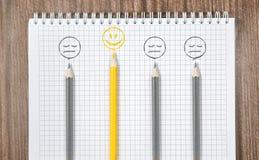 Bleistifte, nettes gelbes Lächeln und trauriges graues Lächeln Stockfoto