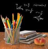 Bleistifte, Notizbücher, Pfirsich und Student verschalen Lizenzfreie Stockbilder