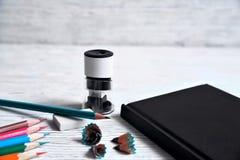 Bleistifte, Notizblock, Bleistiftspitzer, Radiergummi und Schnitzel von den Bleistiften an Stockfotografie