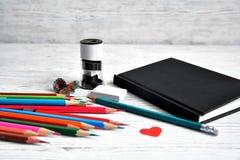 Bleistifte, Notizblock, Bleistiftspitzer, Radiergummi und Schnitzel von den Bleistiften an Lizenzfreie Stockfotos