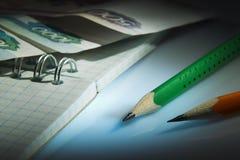 Bleistifte, Notizbuch, Geld Lizenzfreies Stockbild