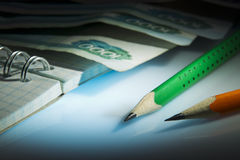 Bleistifte, Notizbuch, Geld Lizenzfreie Stockfotos