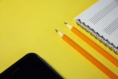 Bleistifte, Notizbuch und Handy auf einem gelben Hintergrund Lizenzfreie Stockfotos