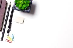 Bleistifte, Notizbuch und Kaktus liegen auf dem Desktop Stockbild