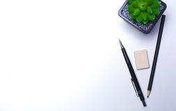 Bleistifte, Notizbuch und Kaktus liegen auf dem Desktop Stockbilder