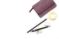 Bleistifte, Notizbuch und Kaktus liegen auf dem Desktop Lizenzfreie Stockbilder