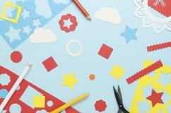 Bleistifte, Scheren und einfache geometrische Formen geschnitten vom farbigen Papier zerstreut stockfotos