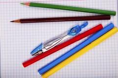 Bleistifte, Stift, Kompass auf Übungsbuchseite Stockbild