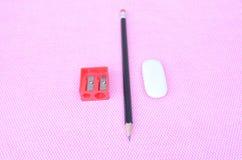 Bleistifte, Stifte, Radiergummi und Bleistiftspitzer gelegen auf den Notizblöcken Stockfotografie