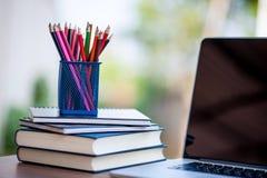 Bleistifte und Bücher werden neben dem Computer gesetzt Lizenzfreies Stockfoto