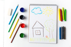 Bleistifte und Bürsten, die um scketchbook mit Kinderzeichenstiftzeichnung liegen Lizenzfreies Stockbild