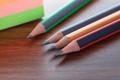 Bleistifte und Blätter auf einer braunen Tabelle, einem Werkzeug für das Zeichnen und abgehobenem Betrag Stockfoto