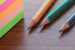 Bleistifte und Blätter auf einer braunen Tabelle, einem Werkzeug für das Zeichnen und abgehobenem Betrag Stockfotografie