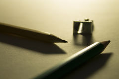 Bleistifte und Bleistiftspitzer auf dem Papier in der Hintergrundbeleuchtung Stockfotos