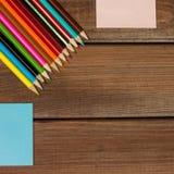 Bleistifte und Briefpapiere auf einem Hintergrund von dunklen hölzernen Tabellen Lizenzfreies Stockfoto