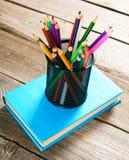Bleistifte und Buch Auf hölzernem Hintergrund Stockbild