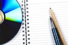 Bleistifte und Cd auf Notizblock Stockfotografie