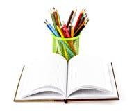 Bleistifte und ein Buch Lizenzfreie Stockfotos