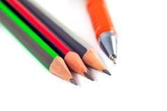 Bleistifte und ein Stift auf einem weißen Hintergrund Lizenzfreie Stockfotos