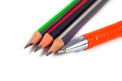 Bleistifte und ein Stift auf einem weißen Hintergrund Stockfotografie