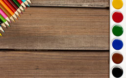 Bleistifte und Farben auf einem Hintergrund des dunklen Holzes Stockbilder
