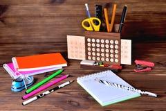 Bleistifte und Kalender auf braunem hölzernem Hintergrund Stockbilder