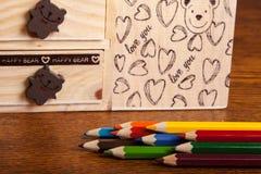 Bleistifte und Kasten auf hölzernem Hintergrund Stockfotografie